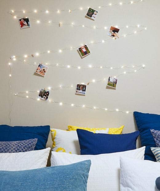 Rangkaian lampu dan foto yang diatur zig-zag di dinding di atas tempat tidur yang penuh dengan bantal.