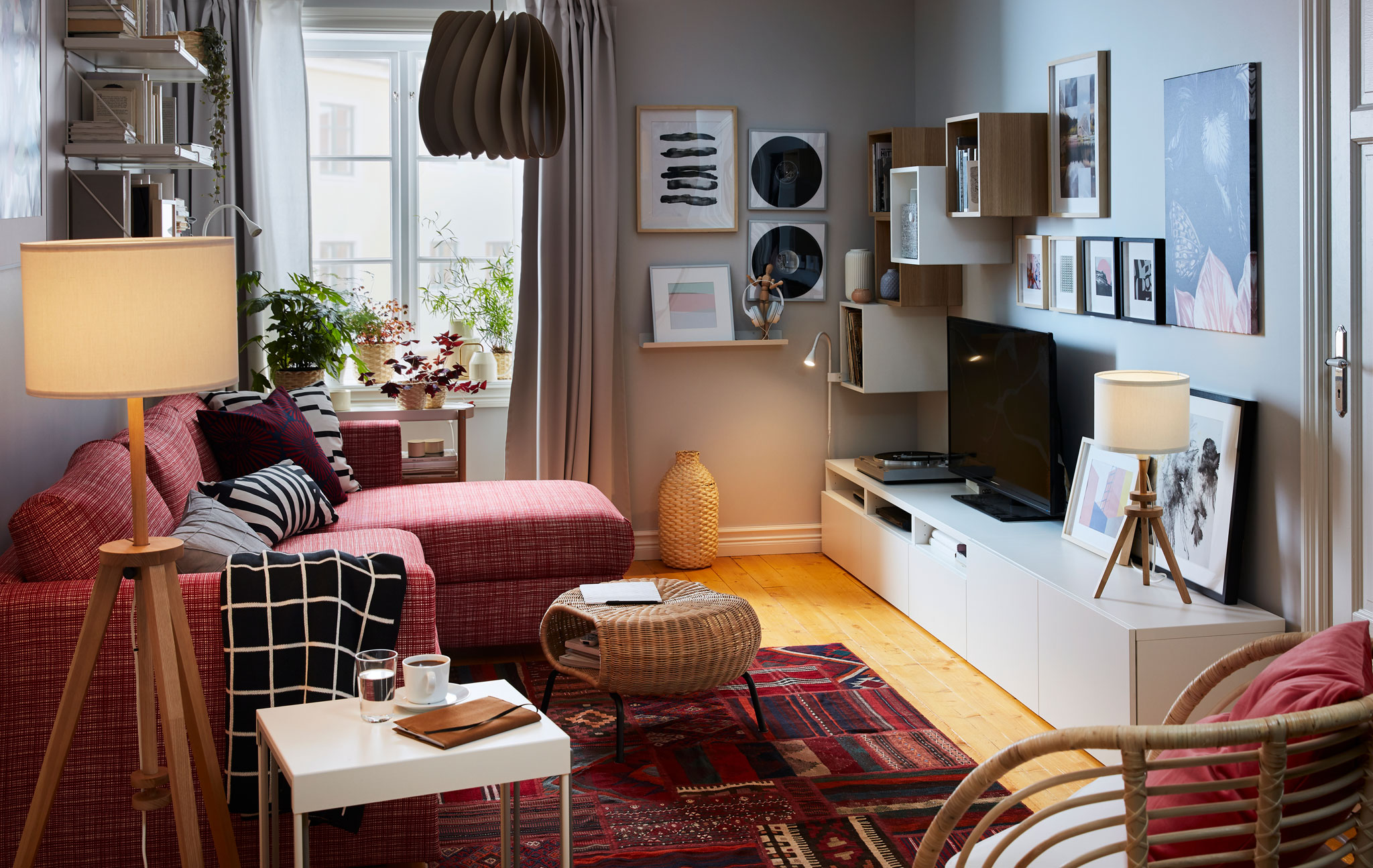 Ruang tamu berukuran kecil dengan tempat tidur sofa dan kursi malas di satu sisi; lemari bufet, ruang penyimpanan, TV, stereo dan dekorasi seni di sisi lain.