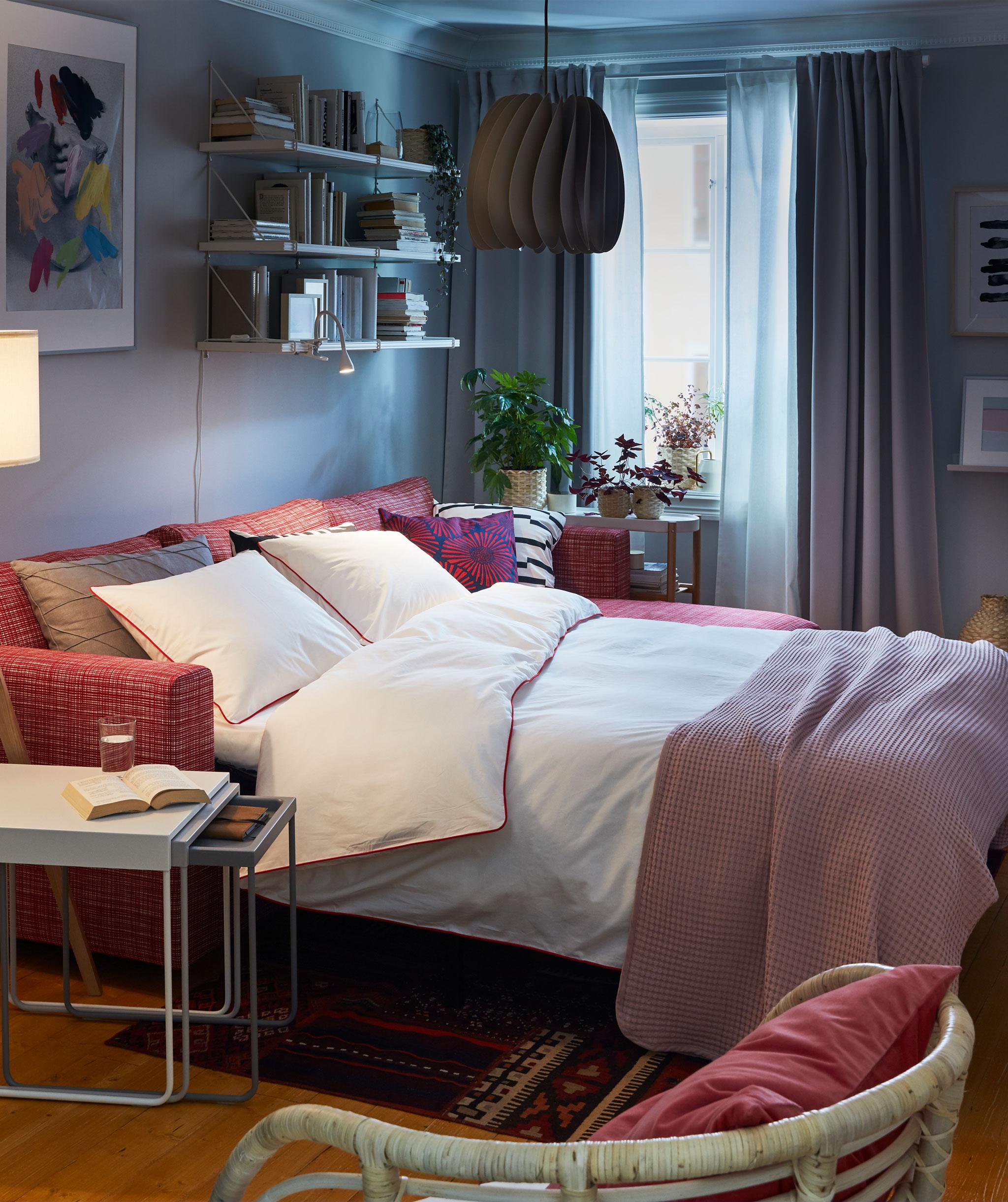 Interior ruang tamu dengan tempat tidur sofa dalam mode tempat tidur ganda. Di sekitarnya: meja tumpuk, tempat duduk, rak buku yang terpasang di dinding.