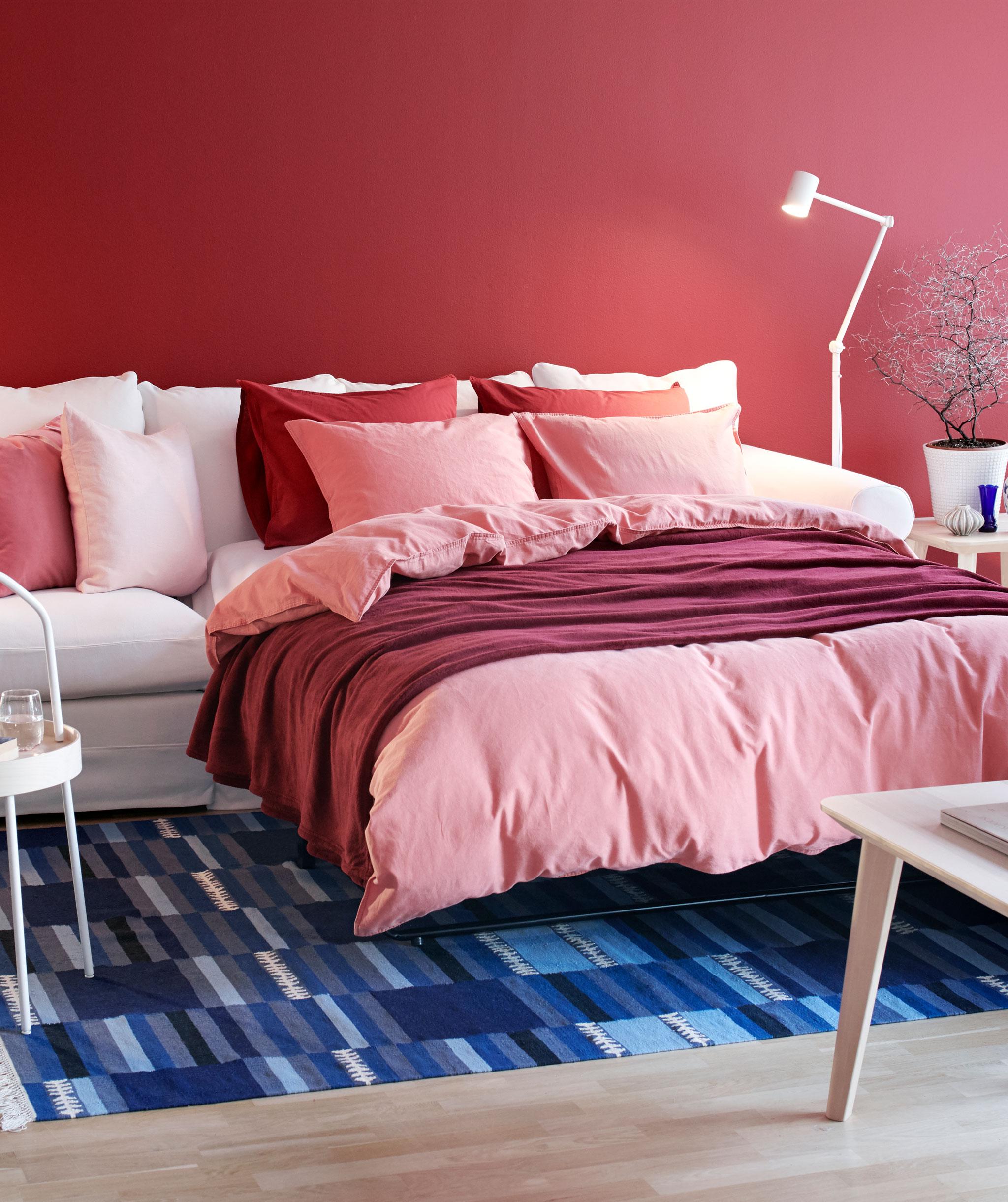 Ruang tamu dengan sofa GRÖNLID diperluas untuk membentuk tempat tidur ganda, dibuat rapi dengan banyak tekstil dan bantal tempat tidur empuk.
