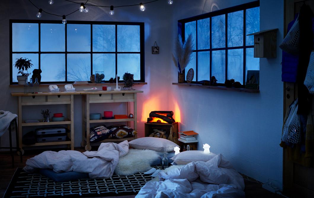 Interior bergaya kabin kayu, kasur di lantai dibuat sebagai tempat tidur sementara, lampu tidur LED diletakkan di sebelahnya.