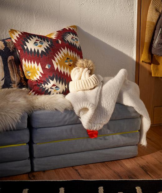 Sebuah tempat duduk dekat dinding dalam bentuk kasur yang dapat dilipat menjadi pouffe; bantal, kulit domba dan baju hangat diletakkan di atasnya.