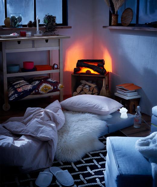 Interior bergaya kabin kayu dengan perapian tiruan dan kasur di lantai sebagai tempat tidur sementara, lampu tidur LED diletakkan di sebelahnya.