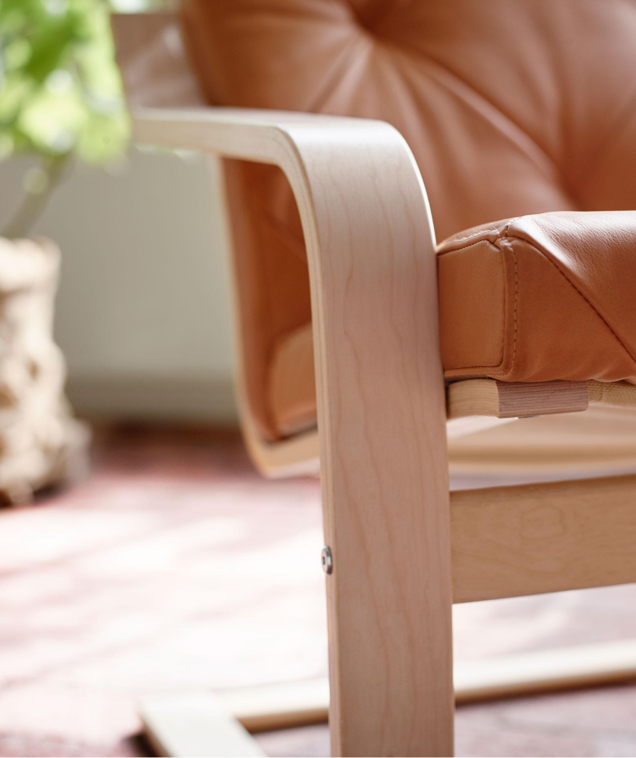Sandaran tangan plywood dan detail rangka serta dudukan dari kursi berlengan, ditempatkan di ruang yang diterangi matahari; tanaman berada di belakang.
