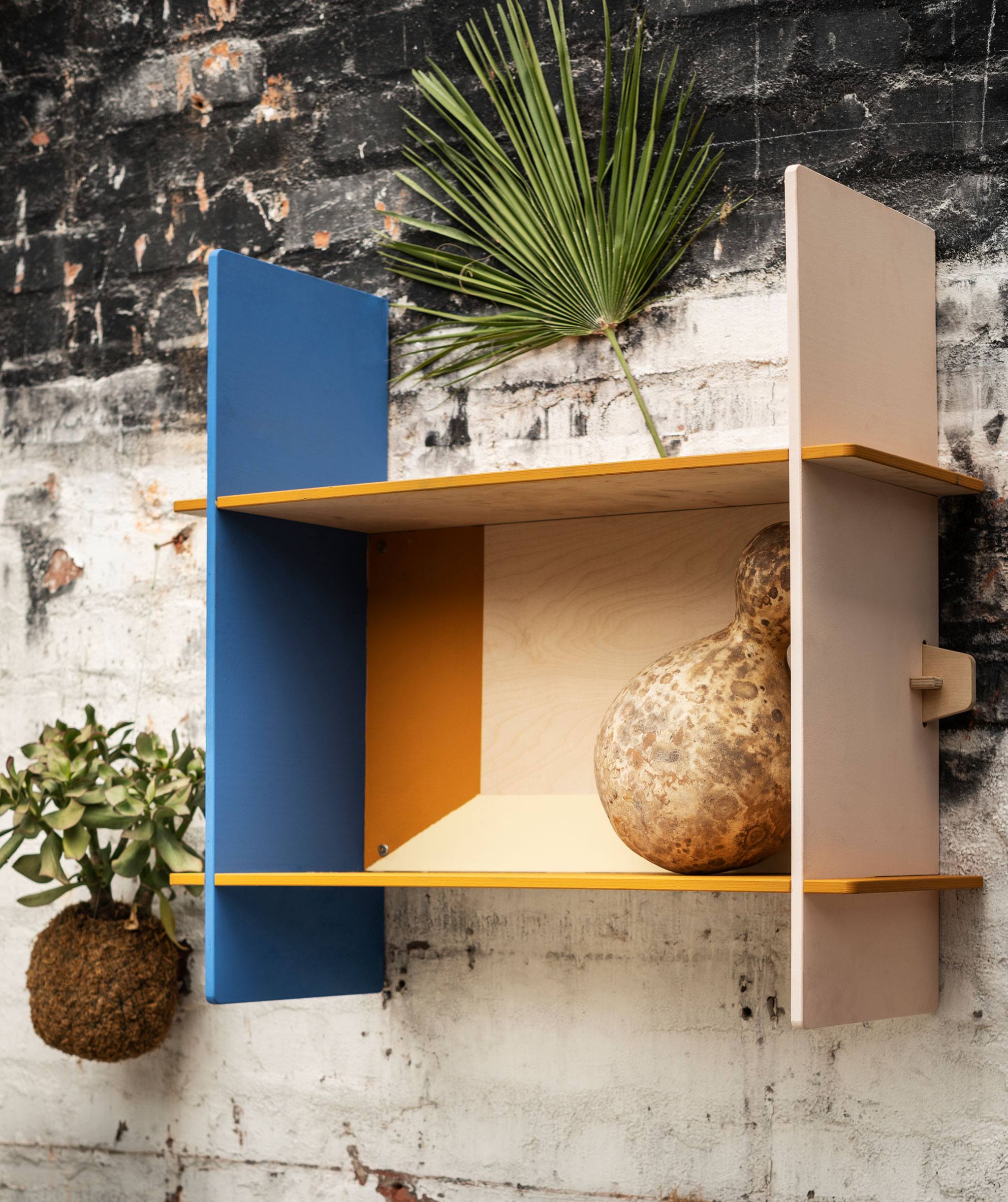Rak dinding kecil persegi panjang yang terbuat dari plywood, dipasang pada dinding bata kasar (mungkin di luar ruangan).