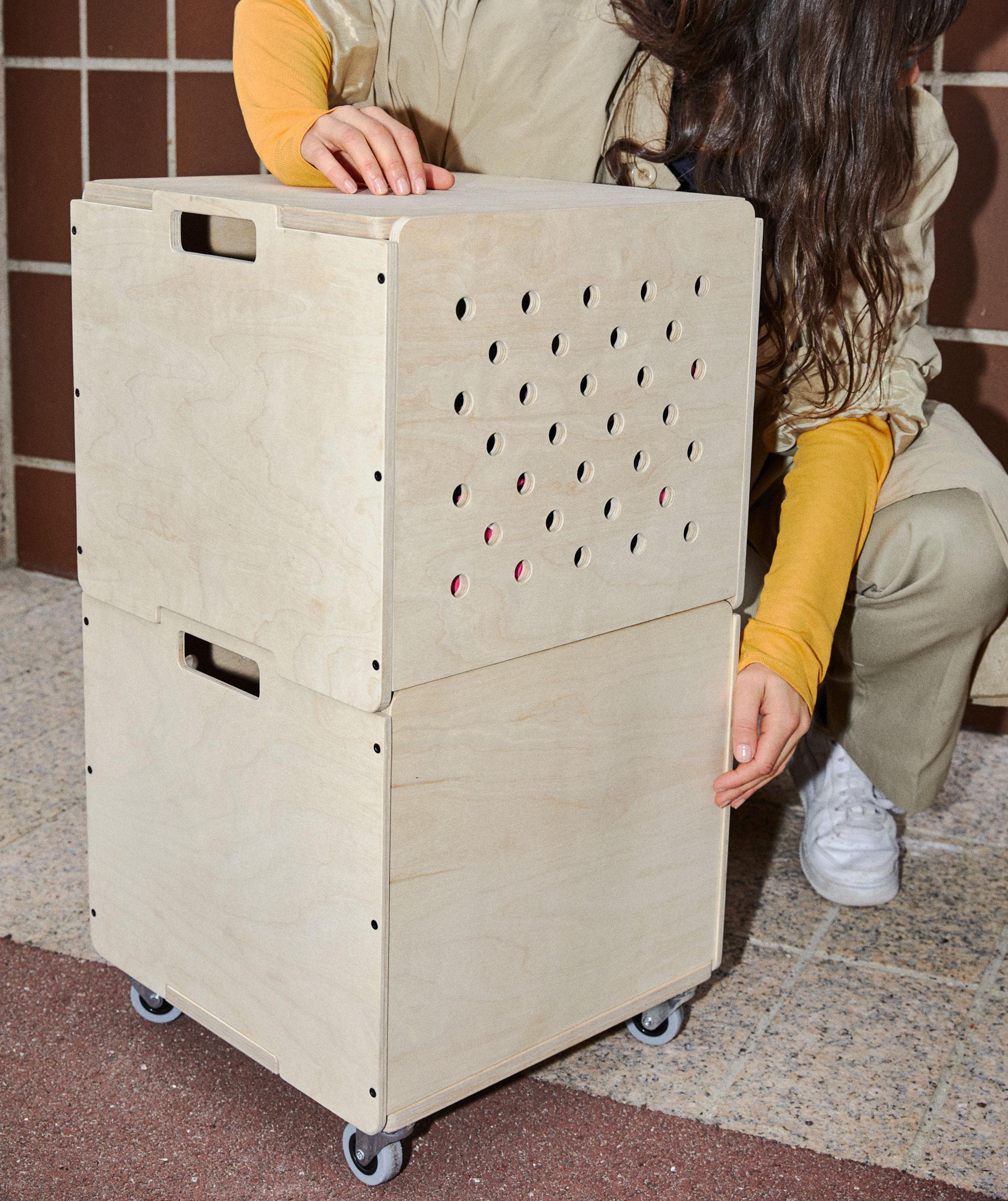 Dua kotak penyimpanan berbentuk kubus yang terbuat dari plywood, ditumpuk satu sama lain. Kotak bawah memiliki roda.