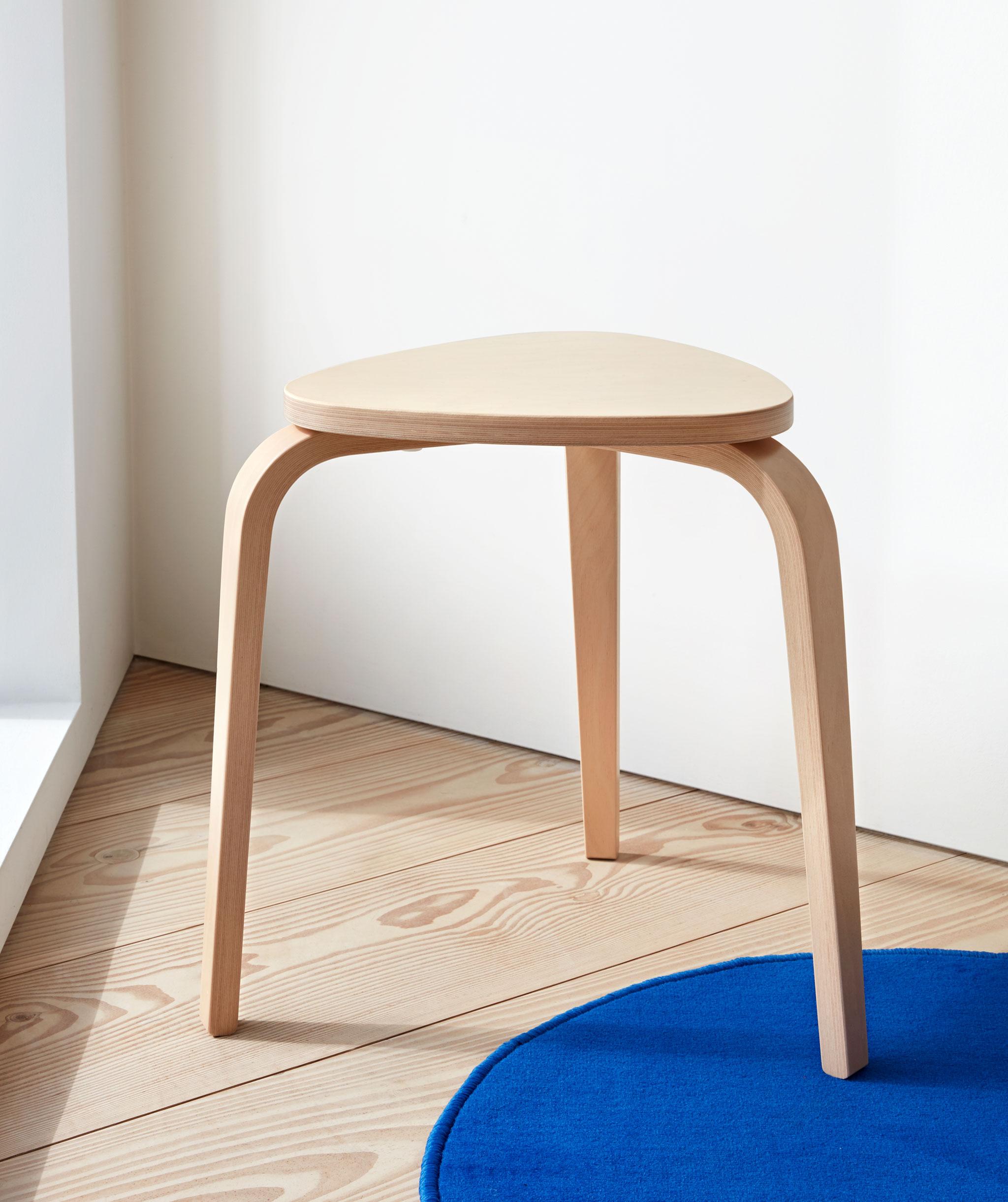 Kursi kayu ringan berkaki tiga berdiri di area sudut dengan lantai kayu, satu kaki berada di karpet biru kecil.