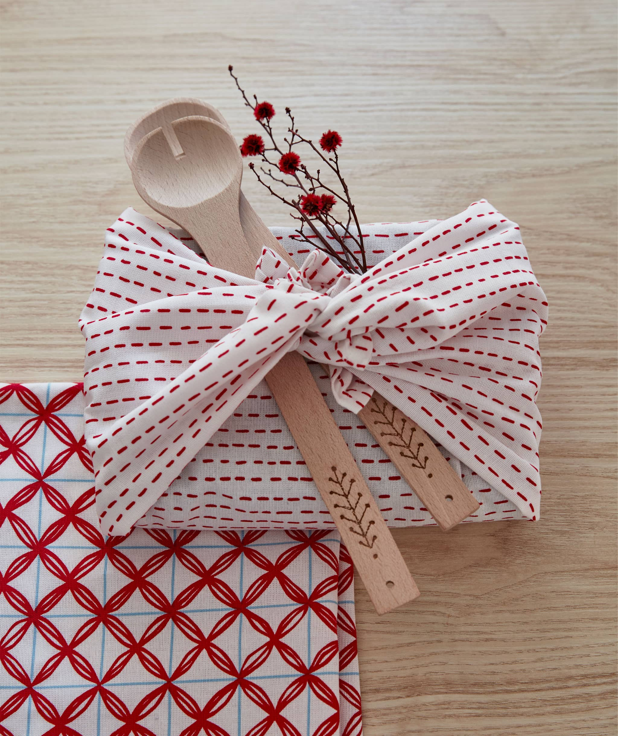 A rectangular gift wrapped not in paper but in a tied piece of cloth, decorated with wooden utensils and a blooming twig.