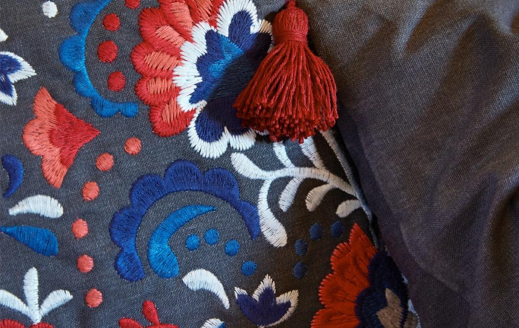 Fokus ke sarung bantal, memiliki detail sulaman yang rumit, dengan corak aneka warna dan rumbai yang tergantung di sudut bantal.