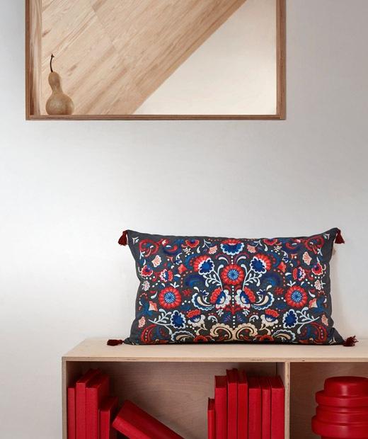 Area dinding dengan cermin dan rak buku rendah berdiri berdampingan; sebuah bantal sulam penuh warna ditempatkan di atas rak.