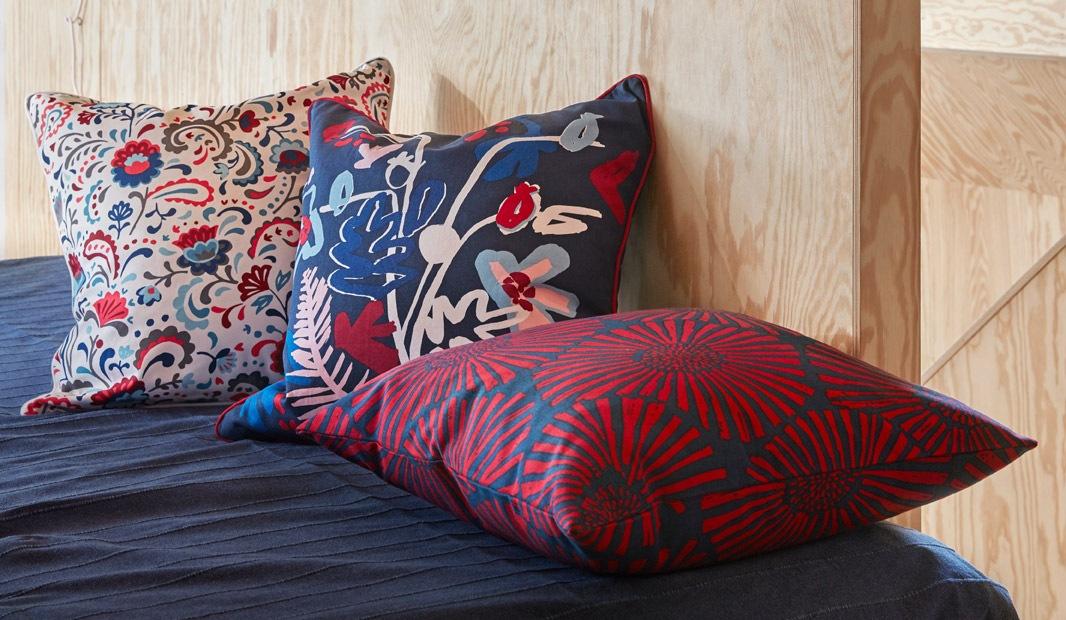 Ujung atau sisi tempat tidur terbuat dari dinding berpanel plywood. Tiga bantal bermotif mewah menghiasi tempat tidur.