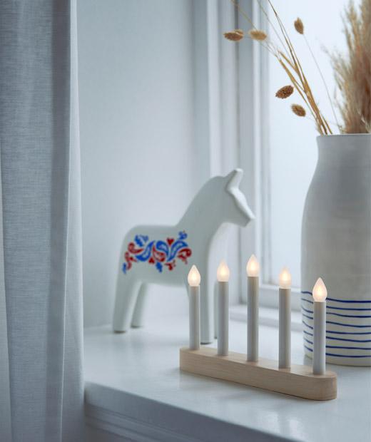 : Ambang jendela didekorasi dengan patung kuda kayu Dalecarlia, sebuah tempat lilin, dan vas keramik dengan rumput kering.
