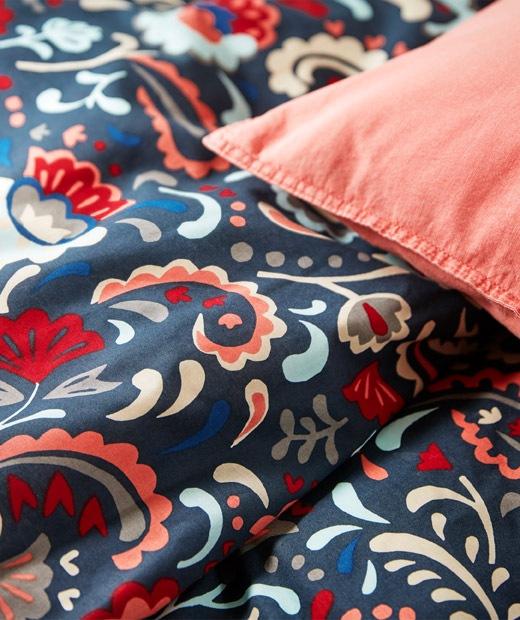 Tempat tidur dilengkapi seprai dalam warna-warna cerah dan dihiasi pola kurbits tradisional Swedia.