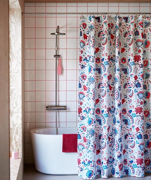 Interior kamar mandi dengan tirai shower penuh corak tergantung di depan bathtub dan shower yang tinggi.
