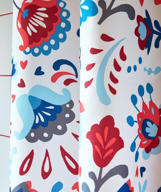 Fokus ke tirai shower, berwarna cerah dan dihiasi pola kurbits tradisional Swedia.
