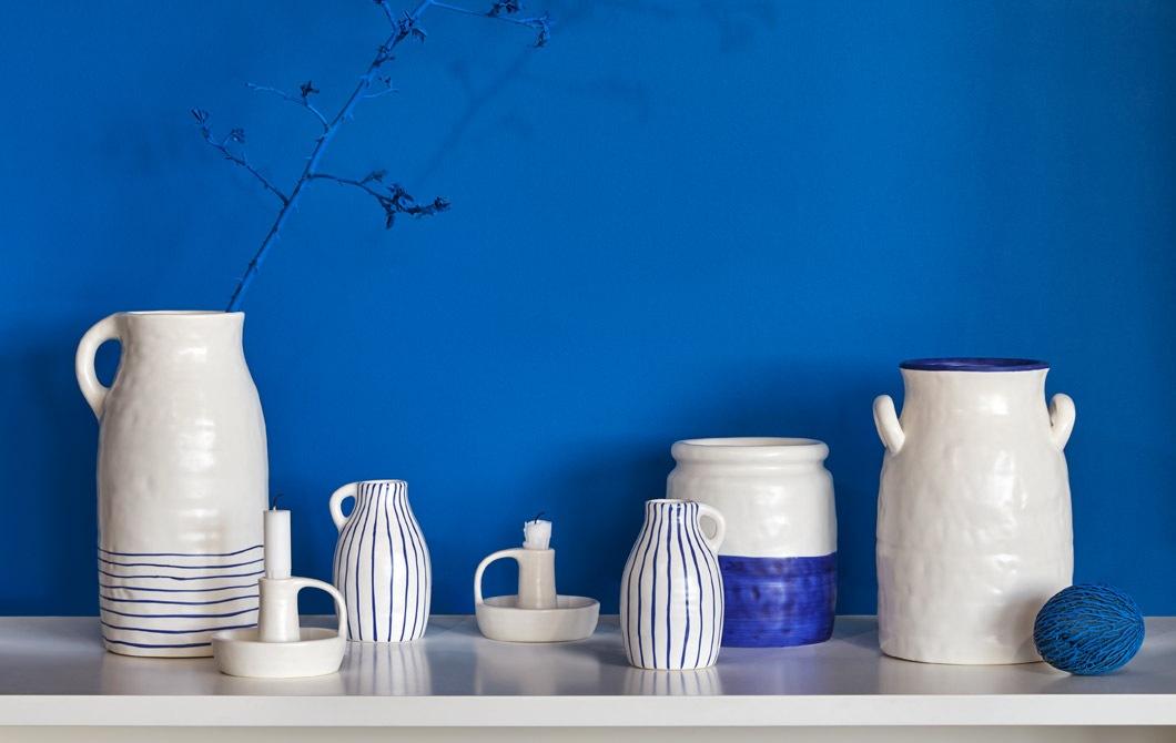 Berbagai vas keramik, pitcher dan tempat lilin dua warna buatan tangan, ditempatkan di atas meja samping.