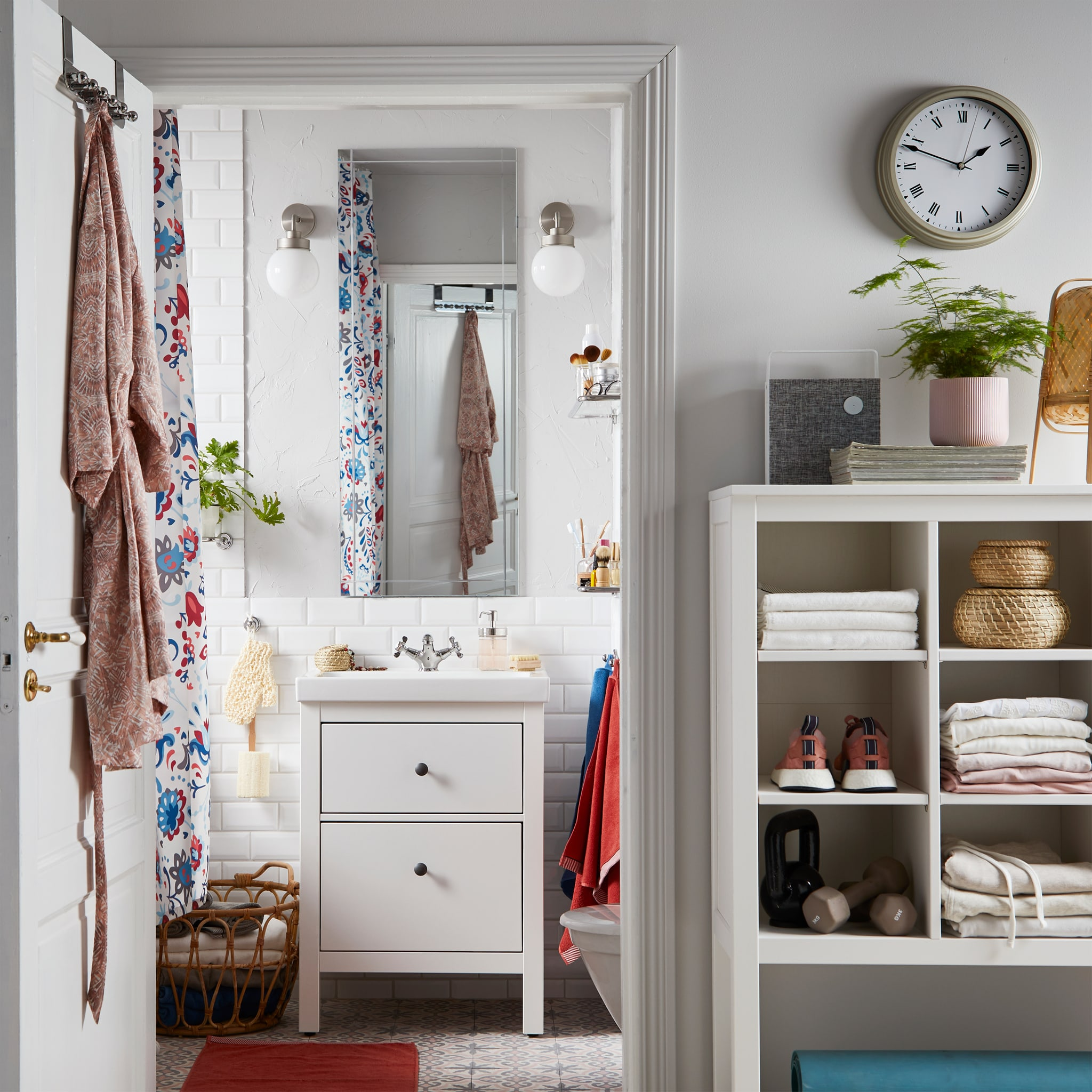An open bathroom door with a hanger with a bathrobe, and inside is a white wash stand, a mirror and wall lamps on each side.