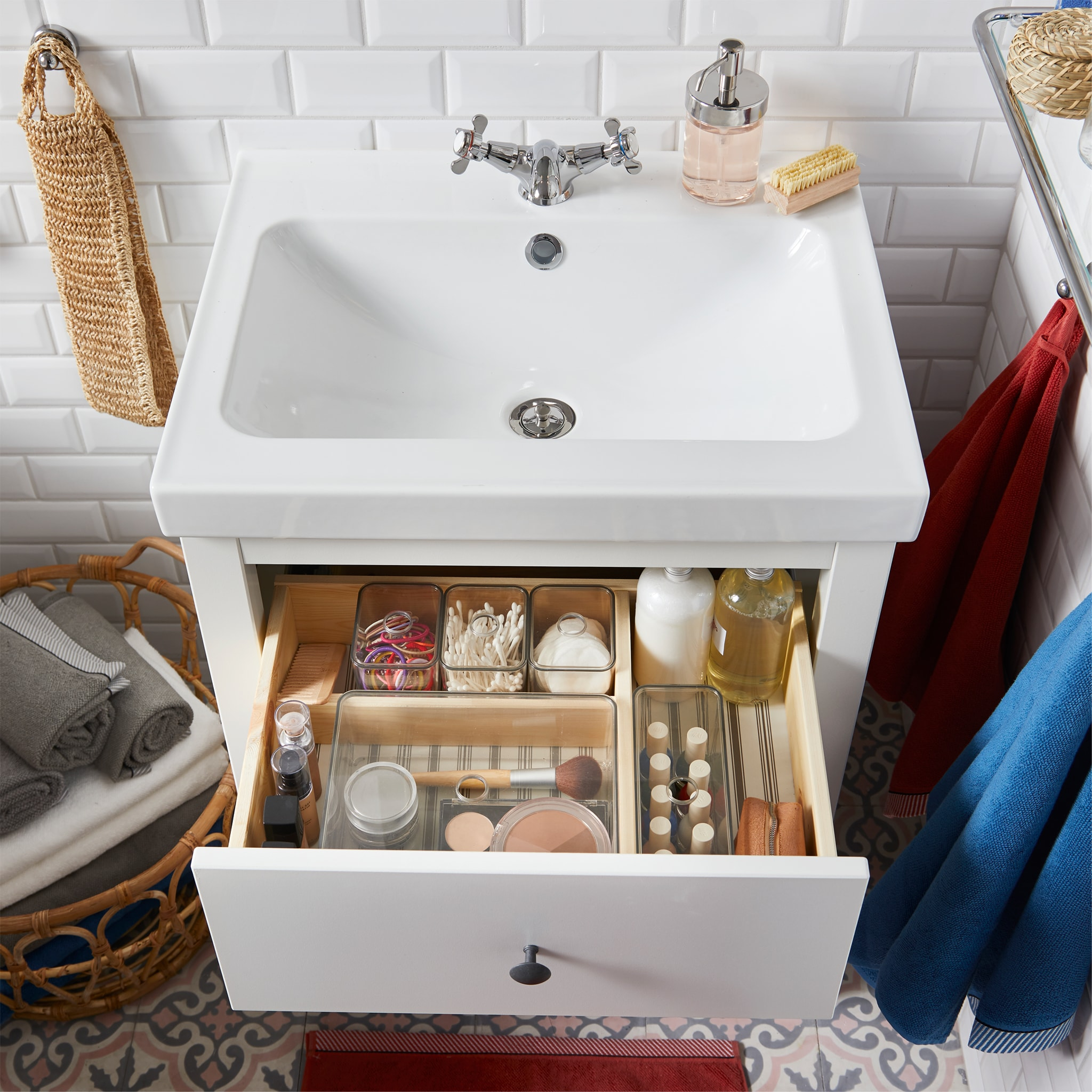 White wash stand with an open drawer and inside is small smoked boxes with lids that store small bathroom items, like makeup.