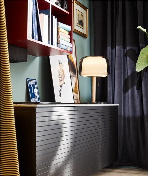 Bagian ruang tamu dengan kabinet rendah yang menempel pada dinding, rak buku dinding, tirai, lampu, dan dekorasi; palet warna yang kaya.