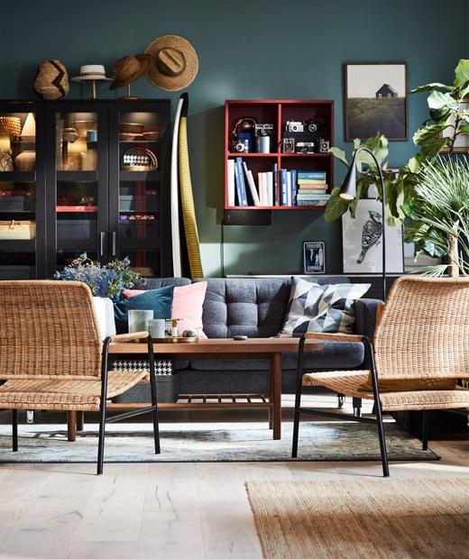 Ruang tamu dengan tempat duduk di sekitar meja kopi, latar belakang dinding dengan banyak penyimpanan terbuka dan pajangan.