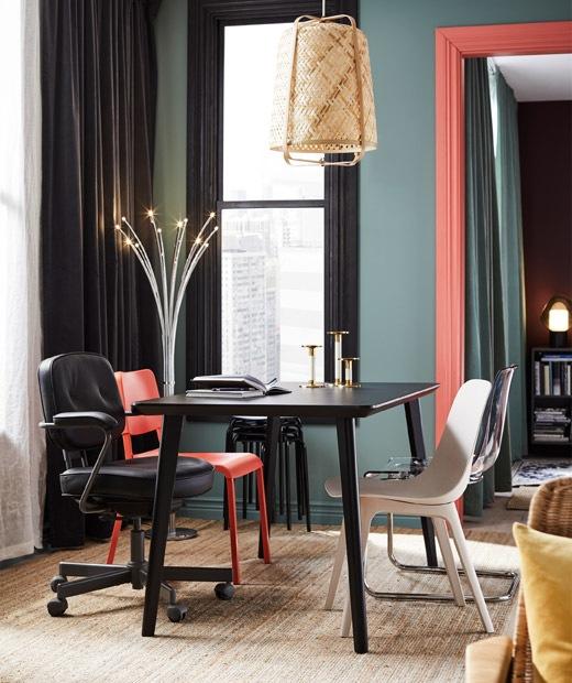Meja makan di ruang tamu dengan kursi-kursi unik. Beragam palet warna  dan aksen yang cerah; pencahayaan dekoratif.