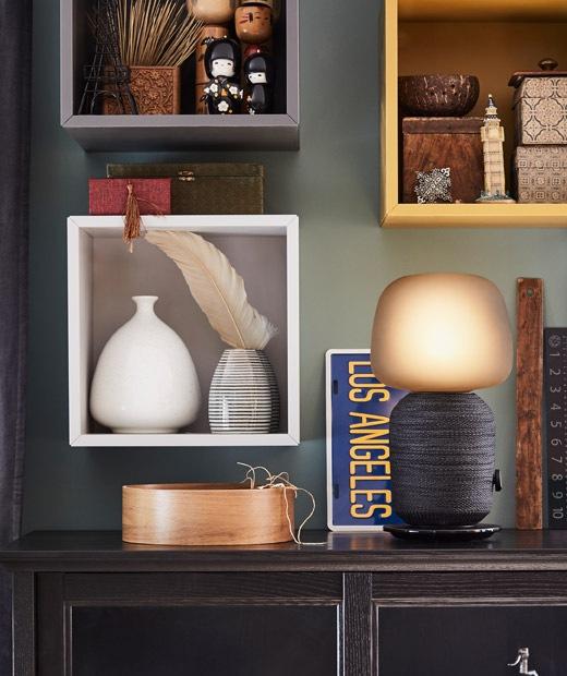 Meja samping dengan kombinasi speaker WiFi dan lampu. Penyimpanan dekoratif di beberapa lemari kecil di dinding bagian atas.
