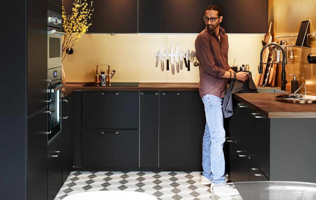 Seorang pria berdiri di dapur berbentuk U dengan nuansa gelap, modern dan sangat bersih. Dengan ubin lantai motif kotak-kotak serta pencahayaan yang cukup.