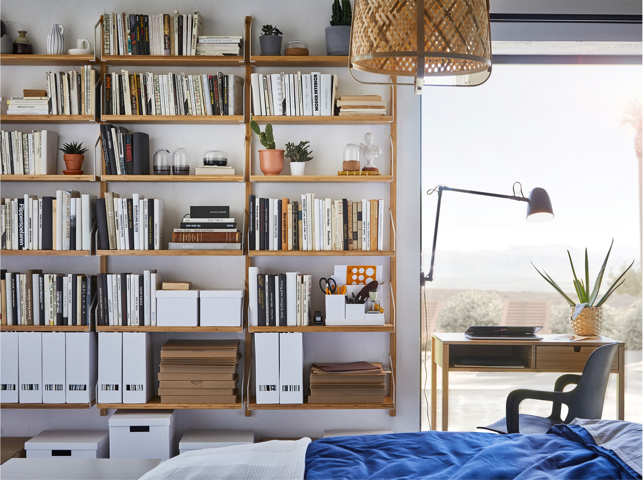 A bedroom with a large wall-mounted shelf combination in bamboo that holds lots of books, plants and decorative items.