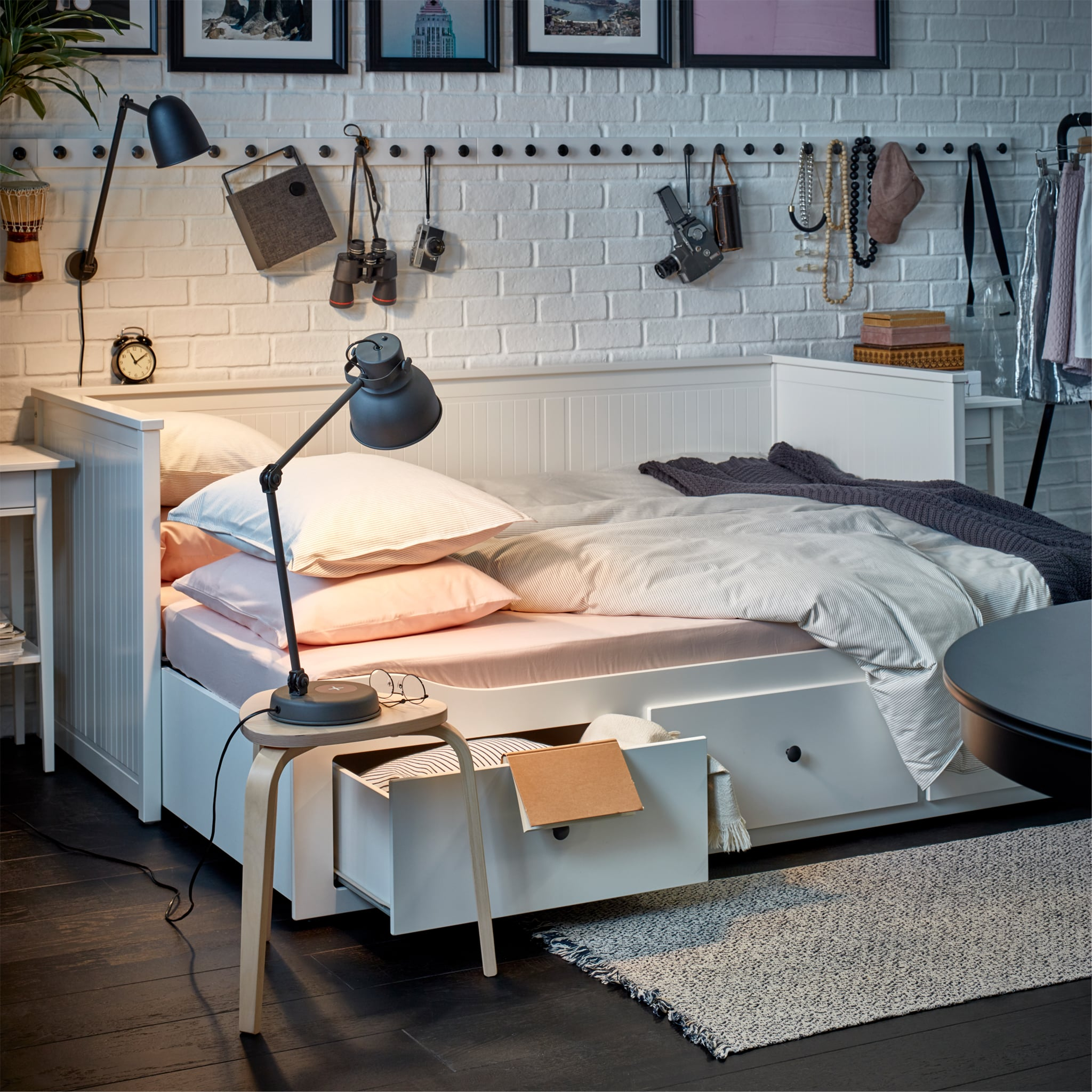 A white daybed that is made as a bed and it's filled with cosy bed textiles and next to it is a stool with a lit table lamp.