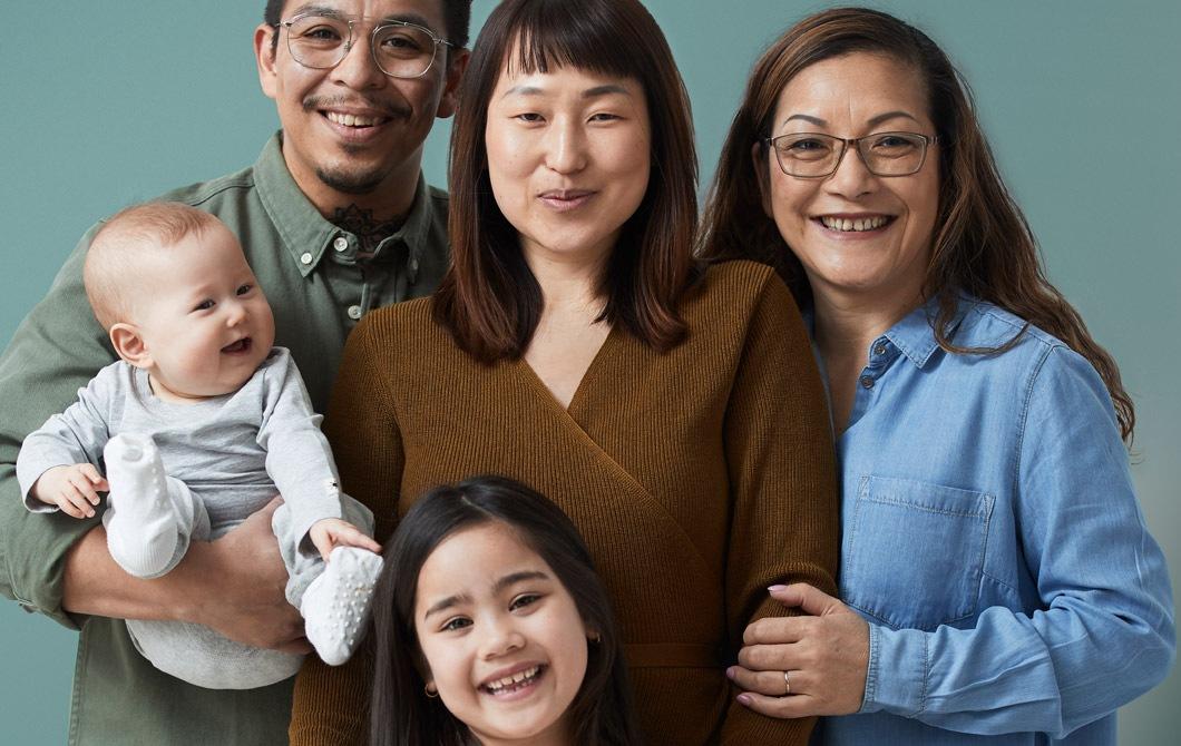 Sebuah keluarga beranggotakan lima orang, semuanya tersenyum mulai dari pasangan suami-isteri dengan bayi serta putri kecil mereka dan seorang nenek berdiri berdekatan.