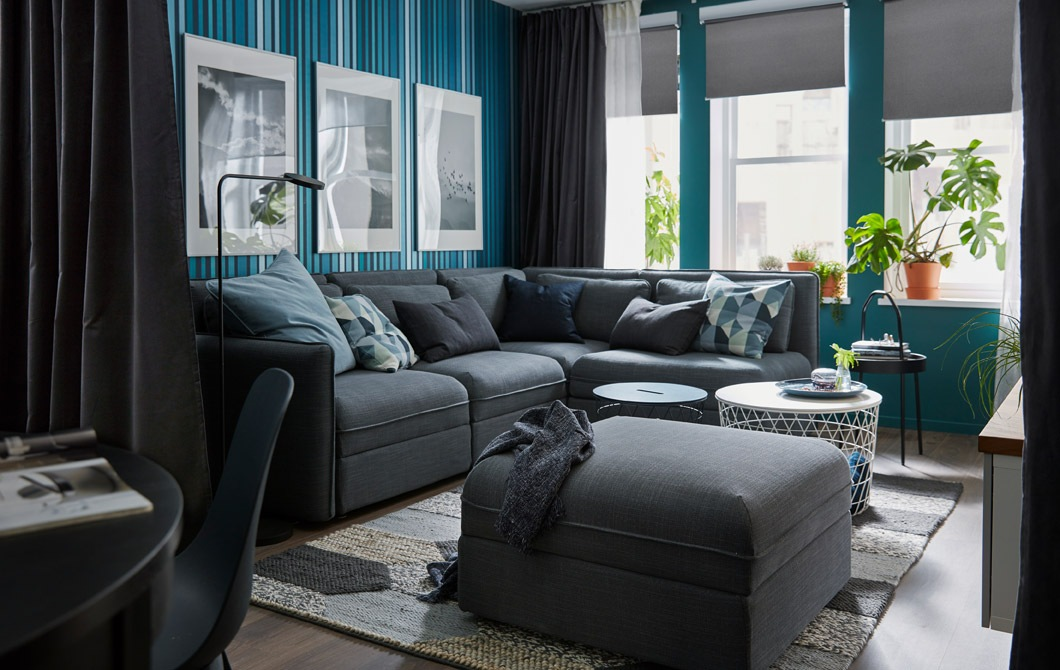 Ruang tamu yang lapang dengan jendela besar; sofa sudut, dinding, dan tirai berwarna teduh; beberapa meja kopi kecil, tanaman.