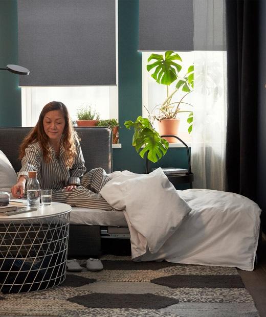 Perempuan dengan piyama duduk di tempat tidur sofa, segelas air di meja kopi, tirai gulung setengah tertutup di belakang.
