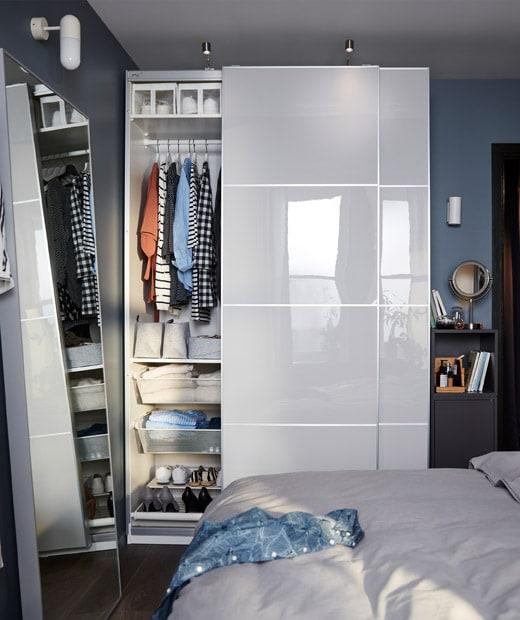 Kamar tidur kecil dengan lemari PAX yang memenuhi dinding, pintu samping yang terbuka memperlihatkan isi lemari yang terorganisir, dan sebuah kabinet kecil.
