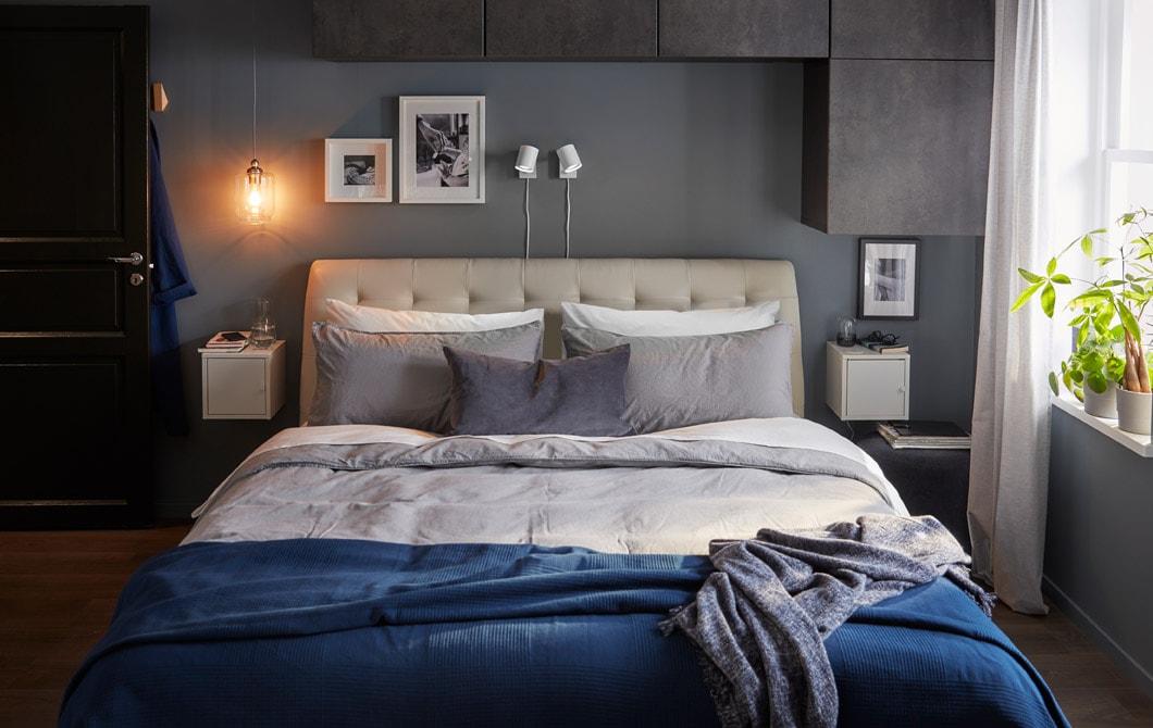 Tempat tidur ganda berukuran besar di kamar tidur bernuansa abu-abu biru. Kabinet dipasang di dinding bagian atas dan di samping tempat tidur, tanaman di jendela.