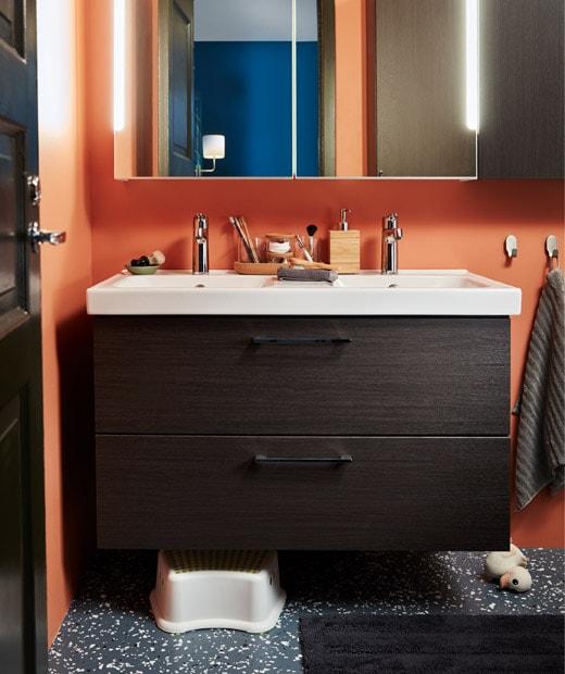 Bagian kamar mandi dengan wastafel ganda dengan laci. Kabinet dengan cermin di bagian atas, bangku anak-anak dan bebek karet di bawah.