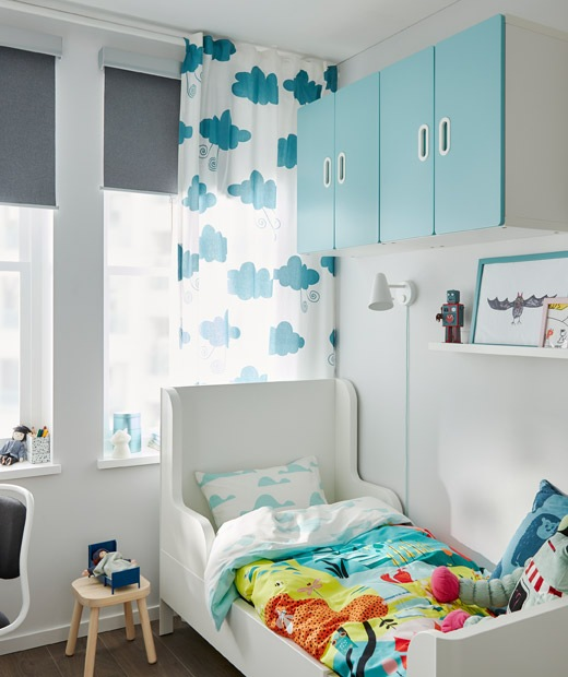 Tempat tidur kecil yang bisa diperpanjang di sudut kamar anak. Seprai dan kabinet dinding penuh warna. Jendela dengan gorden dan tirai gulung.