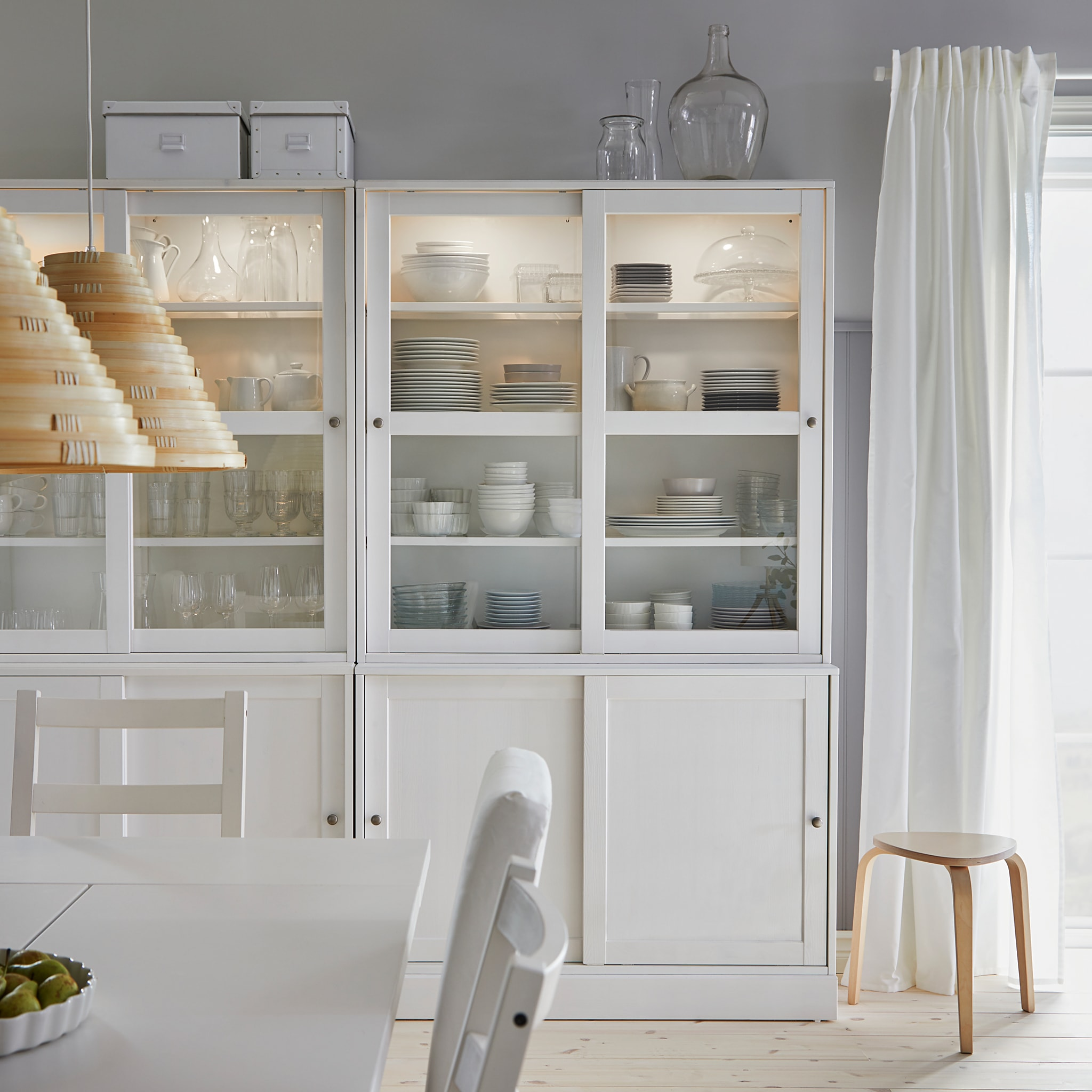 A HAVSTA white storage combination with sliding glass doors store dinnerware and glasses in a dining room.
