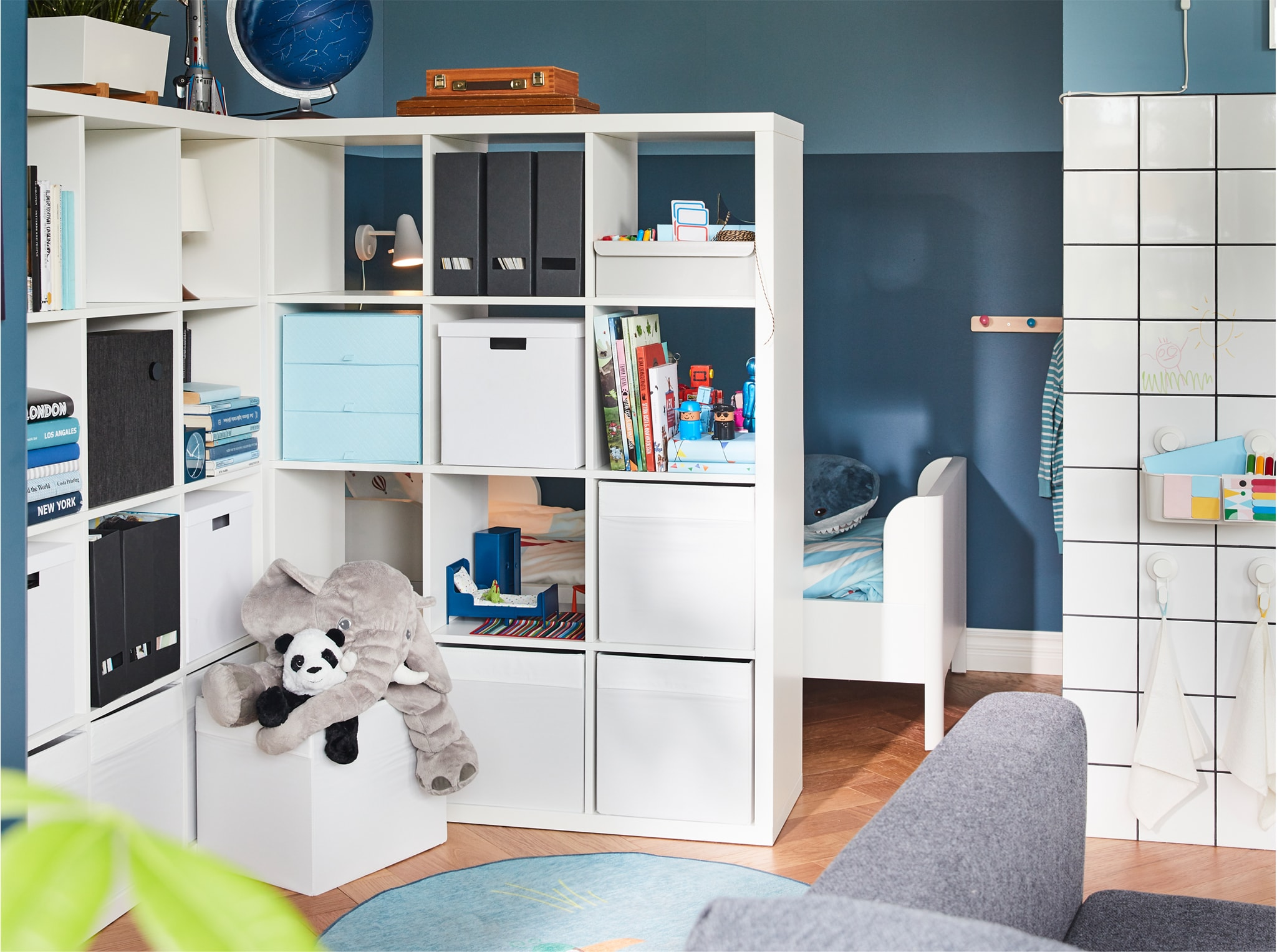 Two shelving units serve as a room divider while offering much storage space. Behind them, you can glimpse a children's bed.