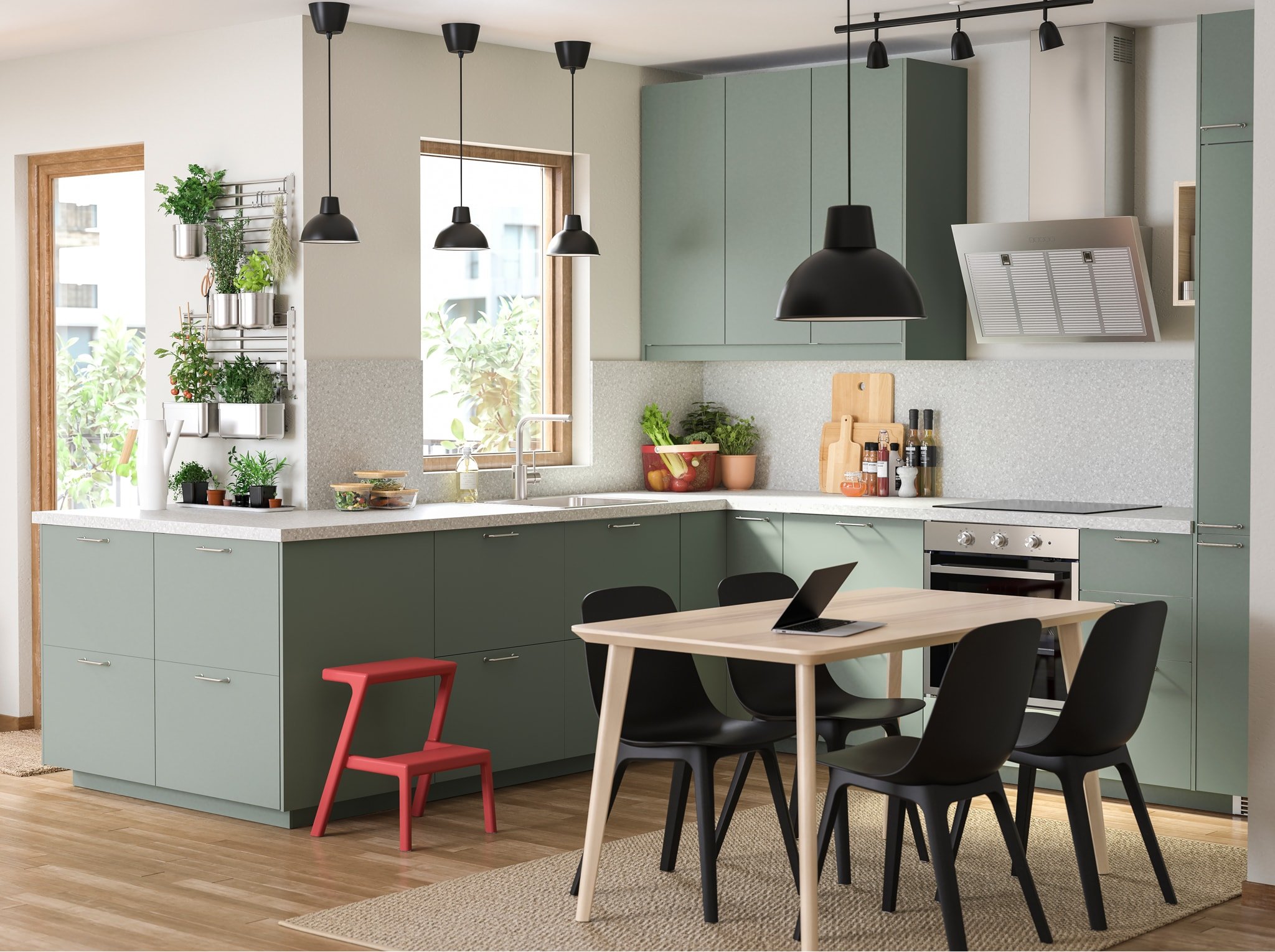 A grey-green kitchen, a wooden dining table, black chairs, a black pendant lamp and lots of herbs that hang on rails.