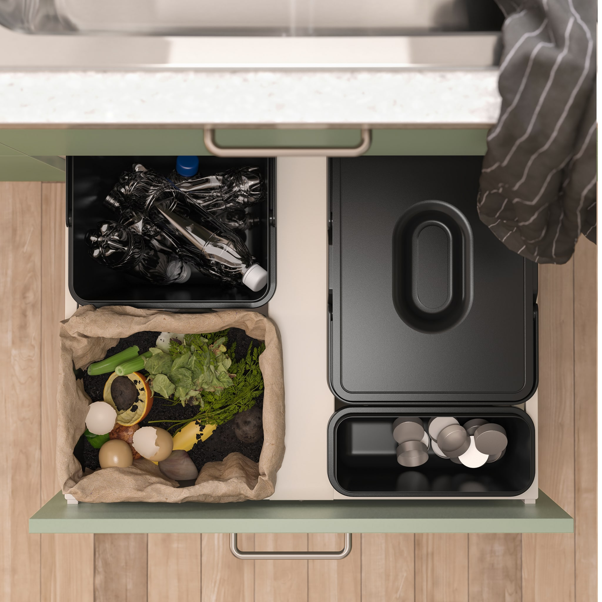 Seen from above is an open kitchen drawer with black waste sorting bins inside. Different kinds of waste is sorted in them.