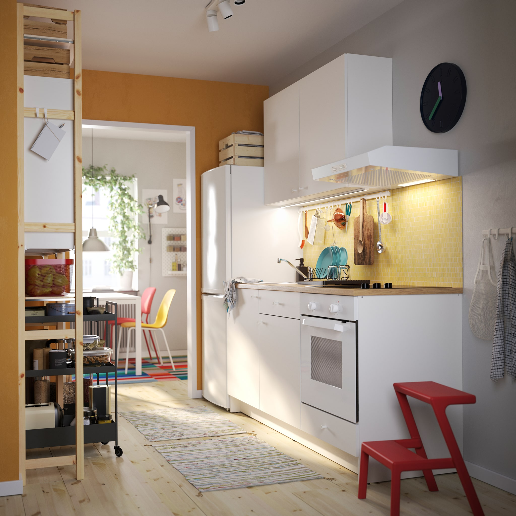 A KNOXHULT kitchen in white, a red step stool, a shelving unit in pine, black trolleys and colourful kitchen chairs.