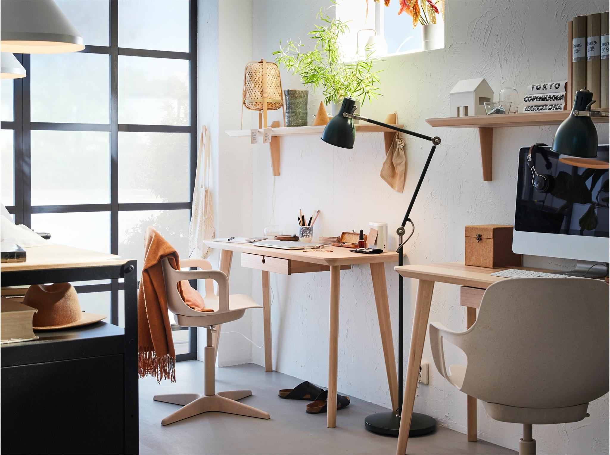 Two desks in ash veneer with white/beige swivel chairs, a black floor lamp between them and two wall shelves in ash veneer.