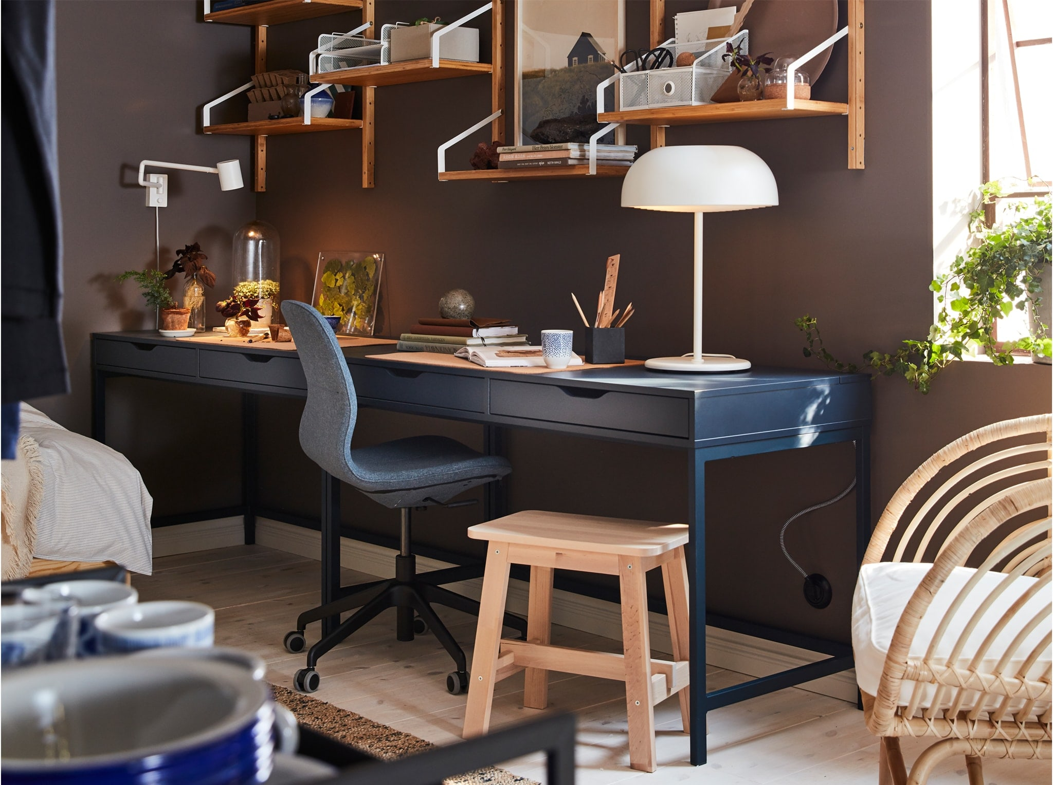Home office with a dark blue desk, a wall-mounted shelf combination in bamboo, a white table lamp and a birch stool.