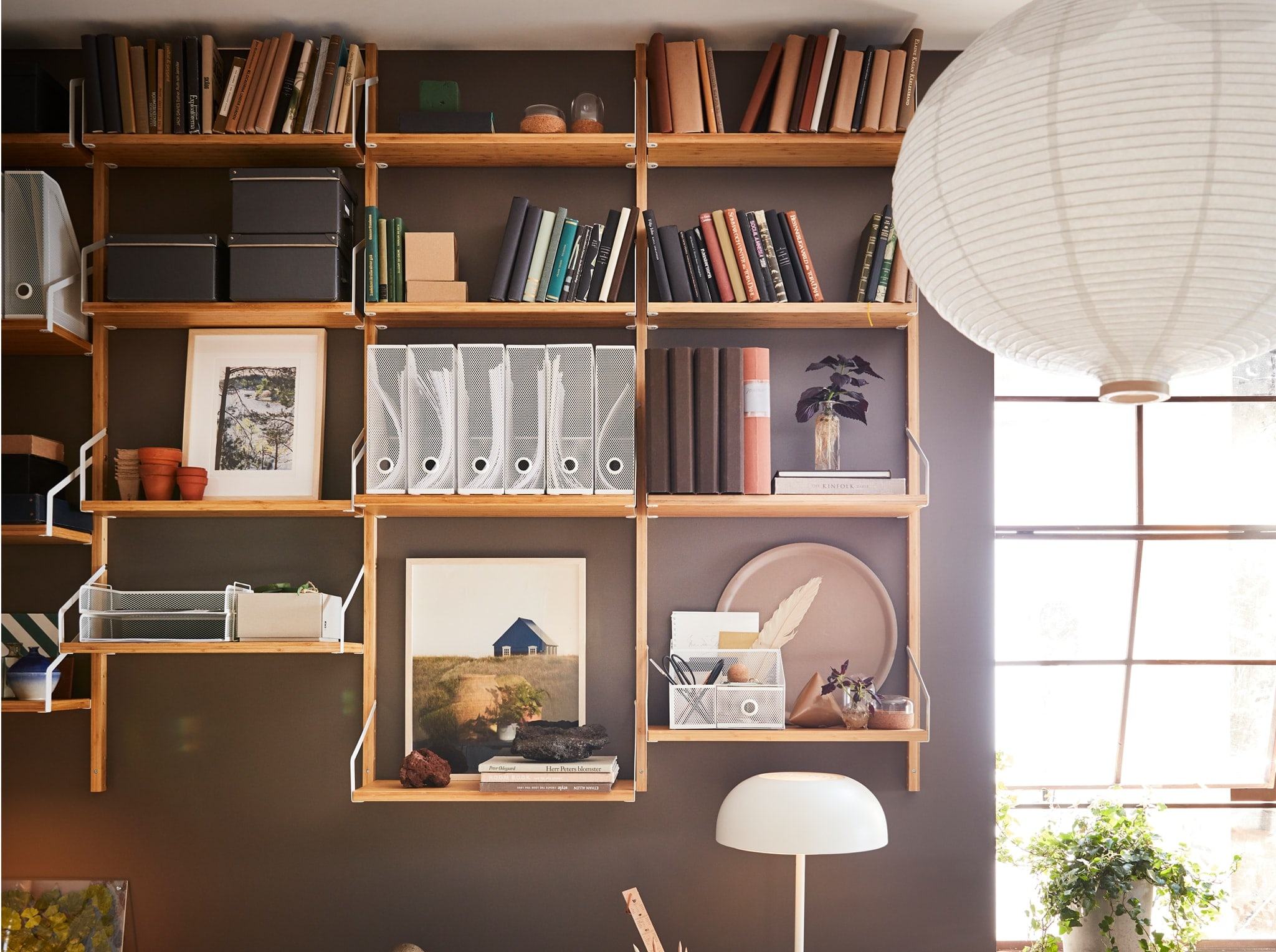 A brown-painted wall with a wall-mounted shelf combination in bamboo with books, decorative items and white magazine files.