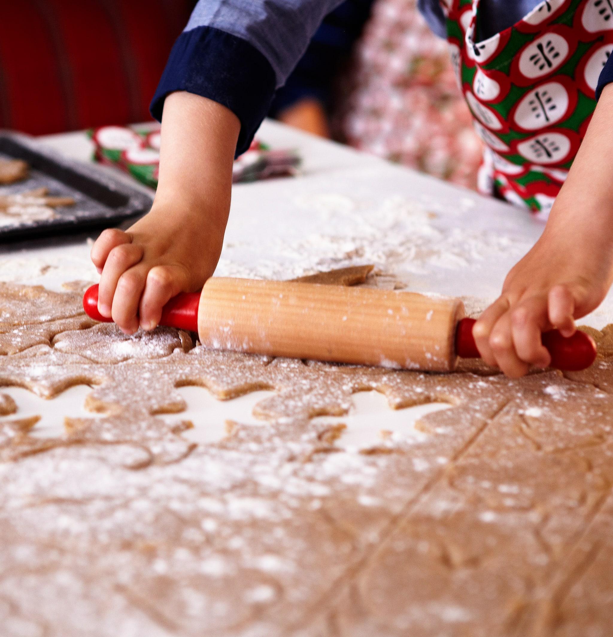Tangan anak yang mengenakan celemek memegang penggiling adonan, mengerjakan selembar adonan kue jahe yang ditaburi tepung yang telah dipotong.