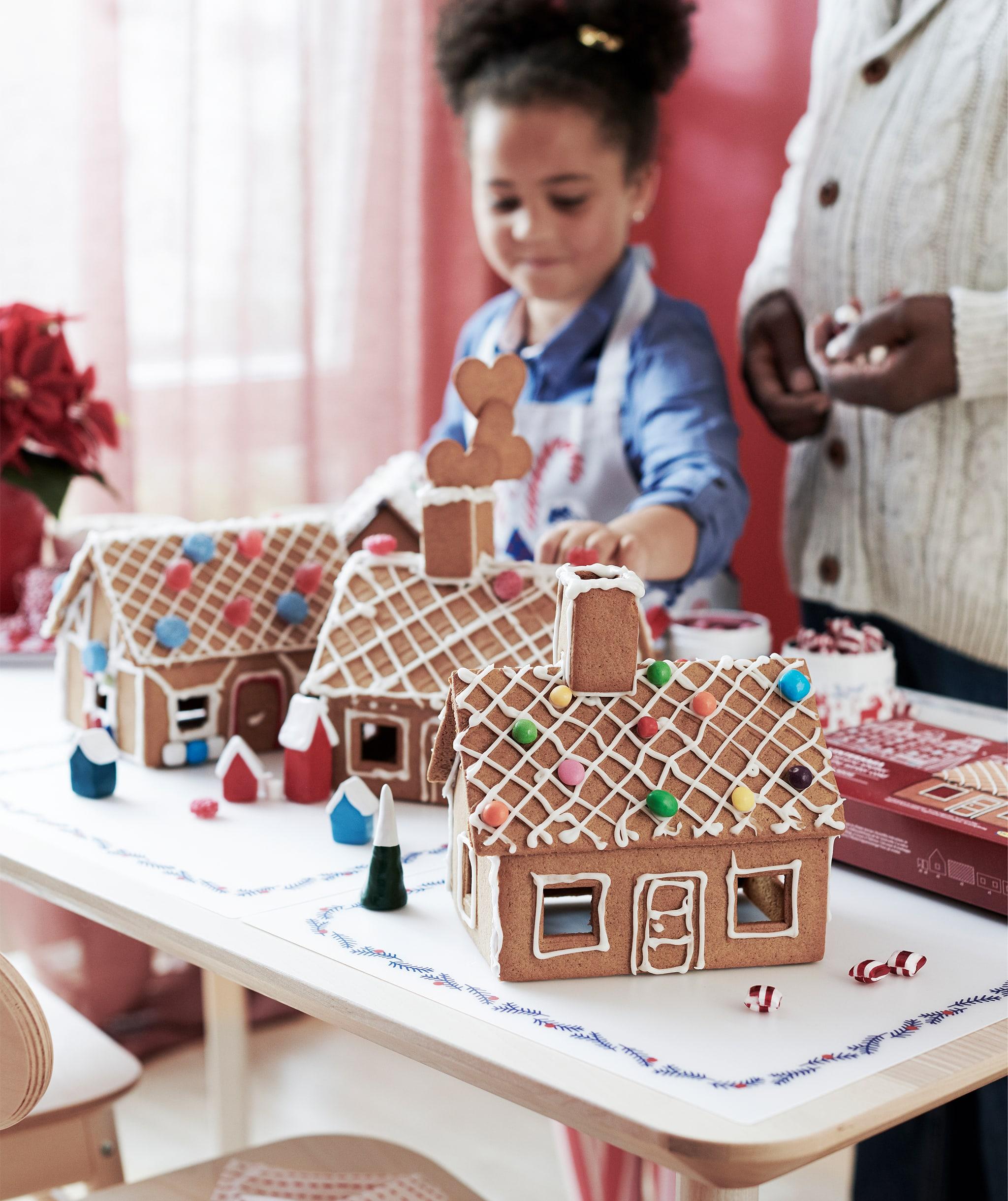 Seorang anak kecil dan orang dewasa berdiri di samping meja tempat meletakkan beberapa rumah kue jahe yang telah selesai dihias dengan rapi menggunakan lapisan gula.