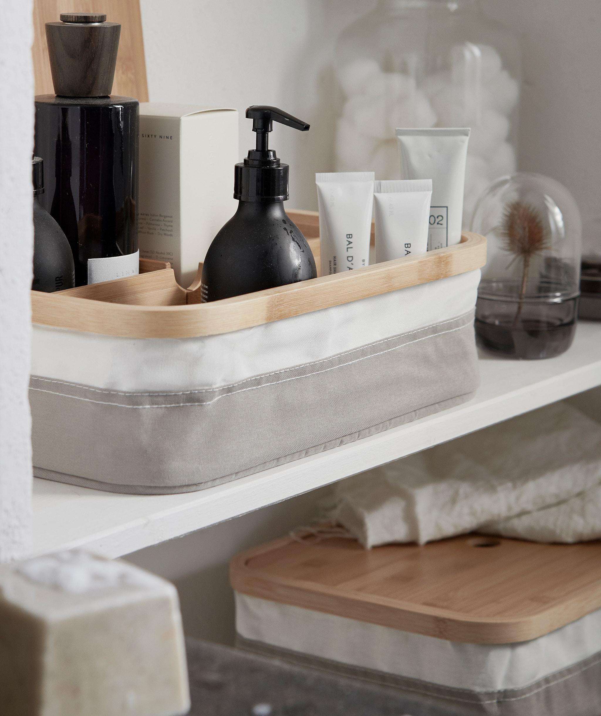 Produk kecantikan ditata dalam kotak dengan kompartemen, diletakkan di rak dinding bersama dengan penyimpanan elegan lainnya.