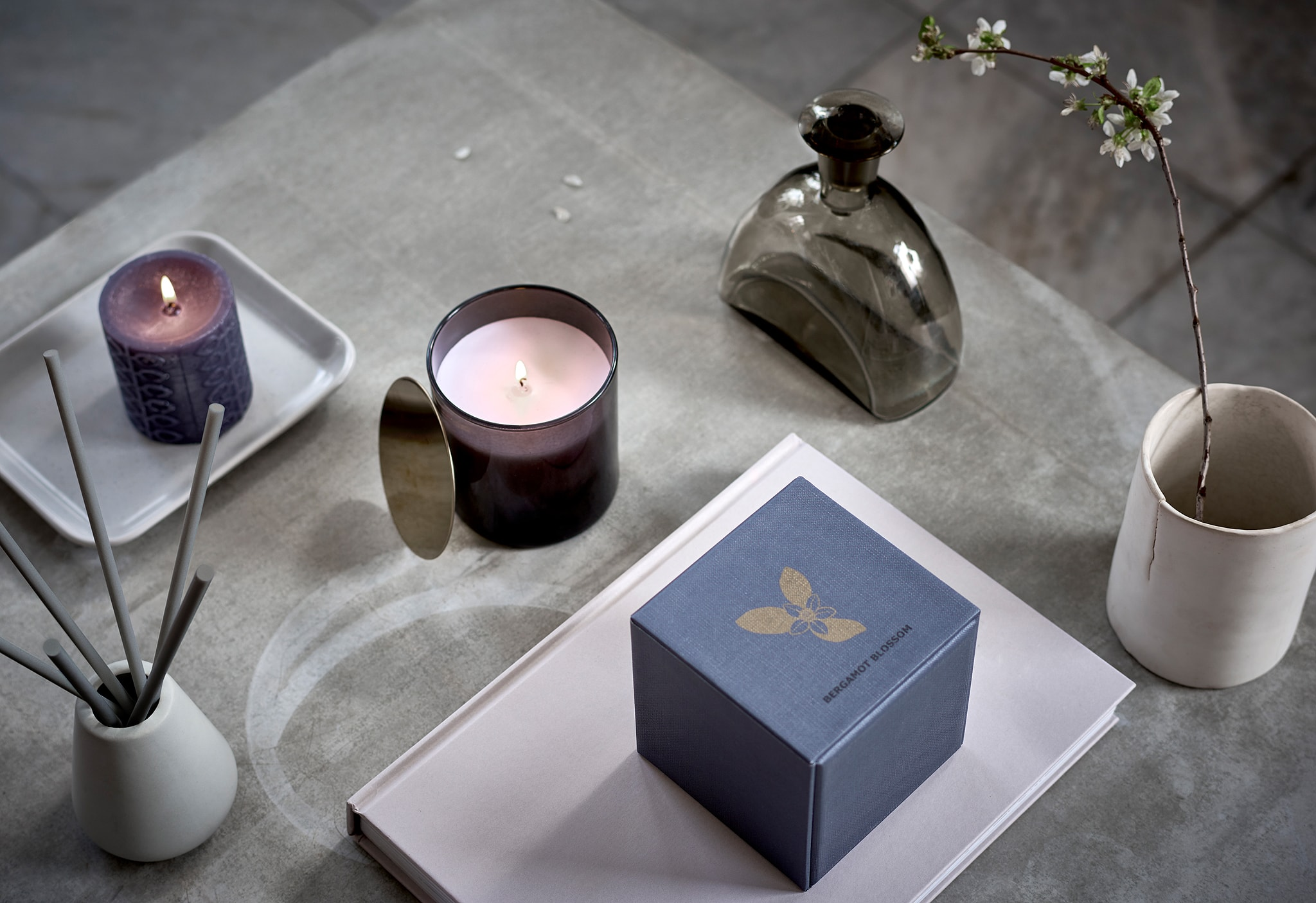 Permukaan dengan susunan lilin beraroma yang ditata simetris, cangkir berisi ranting dan dekorasi bergaya seperti spa.
