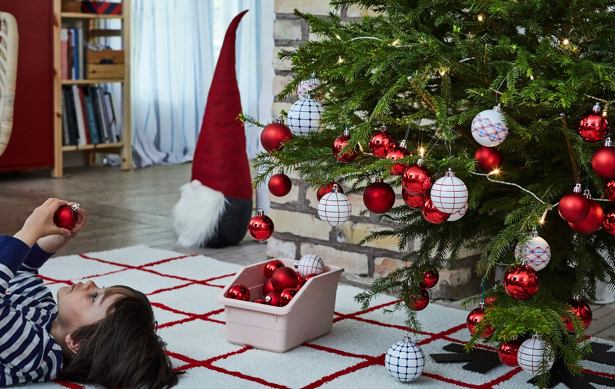 Pohon Natal penuh hiasan dengan seorang anak lelaki berbaring menghadap ke atas di atas karpet di sebelahnya, memeriksa ornamen Natal.