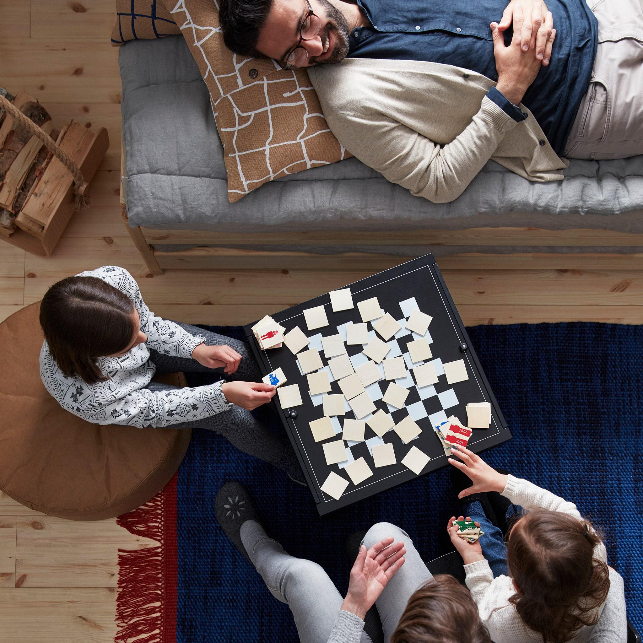 Anggota keluarga yang duduk dan berbaring berkumpul bersama di sekitar permainan yang sedang dimainkan di meja tamu dan papan permainan.